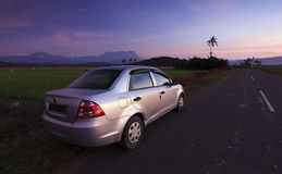 Car parked on roadside at sunset in a rural area Stock Photo