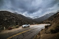 Car parked on scenic mountain wet road curve at rainy cloudy day. Road trip concept.  Stock Photography