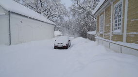 Car parked on the side of the manor. Covered with snow during the snow fall in the winter stock video