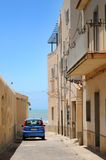 Car parked in street. Car parked in narrow Italian street with sea in background Stock Photo