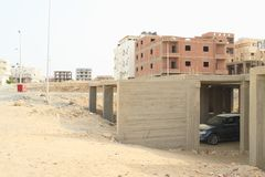 Car parked in unfinished garages in Marsa Alam. Car parked in concrete skeleton of unfinished garages in abandoned house with other building constructions behind royalty free stock photography
