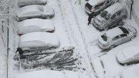 Car parking - cleaning snow from parking stock video footage