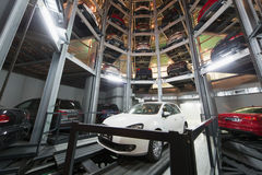 The car on parking lot with automated car parking system. The white car on parking lot with a multi-story automated car parking system Royalty Free Stock Photography
