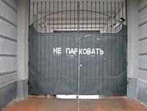 Car parking prohibited warning on gates,. Car parking prohibited message on black metal gates, text on russian language Royalty Free Stock Photo