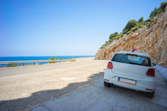 Car Parking in Shade on Route D400 alongside Aegean Sea. A white passenger car is resting in shadow of a hill on Route D400, the famous self-driving road in Royalty Free Stock Image