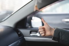 Great ride. Car passenger is showing a thumbs up gesture and is satisfied by a driving of taxi driver stock photo
