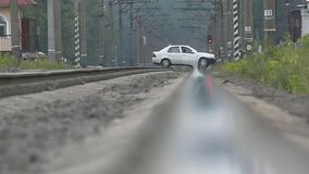 The car passes through the railway crossing in slow motion. The action in the village stock video