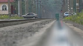 The car passes through the railway crossing in slow motion. The action in the village stock footage