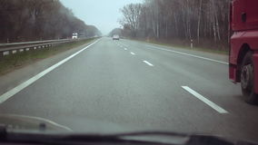 Car passes the truck on highway. Car overtakes the truck on interurban highway. POV view from car cabin to intercity high speed traffic. Outrunning maneuver slow stock video footage