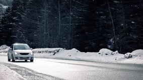 Car Passes On Winter Highway In The Sun. Car passes on bright sunny road through forest in the snow stock video footage