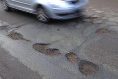 Car passing big potholes Stock Photo