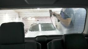 Car passing through the car wash, a person washes the car with a non-contact sink, a view from inside the car. Car passing through the car wash, a person washes royalty free stock photo