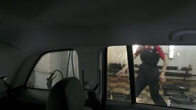 Car passing through the car wash, a person washes the car with a non-contact sink, a view from inside the car. Car passing through the car wash, a person washes royalty free stock images
