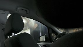 Car passing through the car wash, a person washes the car with a non-contact sink, a view from inside the car. Car passing through the car wash, a person washes royalty free stock image