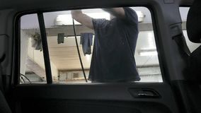Car passing through the car wash, a person washes the car with a non-contact sink, a view from inside the car. Car passing through the car wash, a person washes stock photo