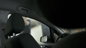 Car passing through the car wash, a person washes the car with a non-contact sink, a view from inside the car. Car passing through the car wash, a person washes stock photos