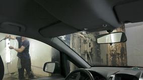 Car passing through the car wash, a person washes the car with a non-contact sink, a view from inside the car. Car passing through the car wash, a person washes royalty free stock photos