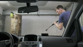 Car passing through the car wash, a person washes the car with a non-contact sink, a view from inside the car. Car passing through the car wash, a person washes stock image