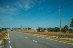 Car passing through countryside road with electric poles. Car passing through countryside road on plain landscape with farms and electric poles, in a sunny day stock photography