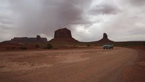 Car passing Monument Valley stock video