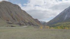 Car passing on a mountain road autumn season 4k. Car passing on a mountain valley road autumn season 4k stock video