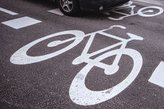 Car passing over bicycle lane sign on the road Royalty Free Stock Photography