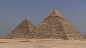 Car passing the two large pyramids in Giza. Car passing pyramids in giza looking very small stock footage