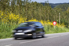 A car passing quickly in front of a road traffic sign Stock Image
