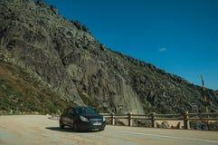 Car passing through a road in rocky landscape. Serra da Estrela, Portugal - July 14, 2018. Car passing through a road in rocky landscape, at the Serra da Estrela stock photo