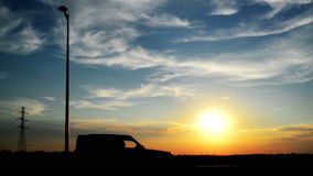 Car passing by in sunset. Silhouette of a vehicle in slow motion. stock video