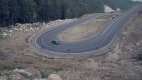 Car passing through winding mountain road, view from top 4k stock video