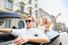Car people - man driving with happy woman. Car people - men driving with happy woman. Male driver wearing sunglasses. Young couple having fun in car driving on Stock Images