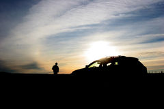 Car/Person Silhouette. Car and driver at sunrise/sunset in an open area; clean, crisp, sharp image Stock Images