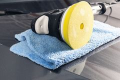 Car polish concept. Buffing and polishing car. Car detailing. Polisher and microfiber cloth on the car. Tools for polishing.  royalty free stock images
