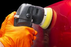 Car polish wax worker hands applying protective tape before polishing. Buffing and polishing car. Car detailing. Man holds a polis. Her in the hand and polishes stock photo