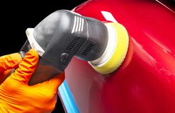Car polish wax worker hands applying protective tape before polishing. Buffing and polishing car. Car detailing. Man holds a polis. Her in the hand and polishes stock photography