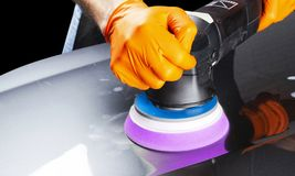 Car polish wax worker hands applying protective tape before polishing. Buffing and polishing car. Car detailing. Man holds a polis. Her in the hand and polishes stock images