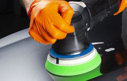 Car polish wax worker hands applying protective tape before polishing. Buffing and polishing car. Car detailing. Man holds a polis. Her in the hand and polishes royalty free stock photos