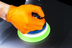 Car polish wax worker hands applying protective tape before polishing. Buffing and polishing car. Car detailing. Man holds a polis. Her in the hand and polishes royalty free stock photo