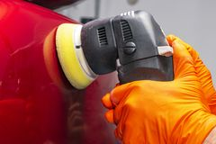 Car polish wax worker hands applying protective tape before polishing. Buffing and polishing car. Car detailing. Man holds a polis. Her in the hand and polishes royalty free stock photography