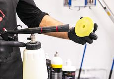 Car polish wax worker hands cleaning polishing sponge before polishing. Buffing and polishing car. Car detailing. Man holds a poli. Sher sponge in the hand royalty free stock image