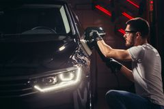 Car polish wax. worker hands holding a polisher. And polish car Royalty Free Stock Image