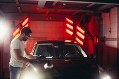 Car polish wax. worker hands holding a polisher. And polish car Stock Photography