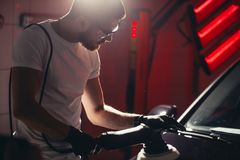 Car polish wax. worker hands holding a polisher. And polish car Royalty Free Stock Images