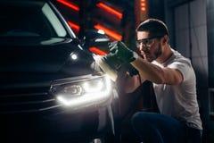 Car polish wax. worker hands holding a polisher. And polish car Stock Photo