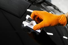 Car polish wax worker hands polishing car. Buffing and polishing vehicle. Car detailing. Man holds a polisher in the hand and poli. Shes the car. Tools for royalty free stock photos