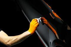 Car polish wax worker hands polishing car. Buffing and polishing vehicle with ceramic. Car detailing. Man holds a polisher in the stock image