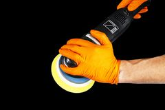 Car polish wax worker hands withs tools isolated on black background. Buffing and polishing. Car detailing. Man holds a polisher i. N the hand and polishes stock image
