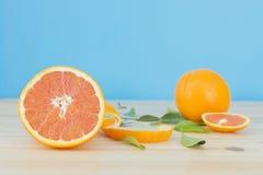 Car pomarańcze na drewnianym stole nad błękitnym tłem Obraz Stock