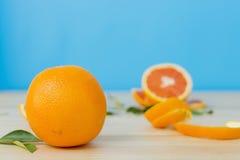 Car pomarańcze na drewnianym stole nad błękitnym tłem Zdjęcie Royalty Free